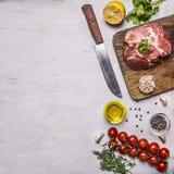 Rå grisköttbiff med kryddor, vitlök och den ört-, citron- och smörkniven för kött, tomater en filial, svartpeppar, dill, gräns, w Arkivfoto