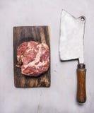 Rå grisköttbiff på en skärbräda- och tappningköttköttyxa på trälantligt slut för bästa sikt för bakgrund upp Royaltyfri Fotografi