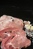 Rå grisköttbiffar med salt, peppar och vitlök på mörk träbaksida royaltyfri bild