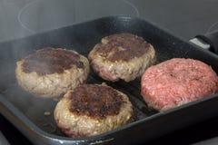 Rå grisköttbiffar med salt, peppar och vitlök på mörk träbaksida fotografering för bildbyråer