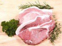 Rå grisköttbiffar och örter Royaltyfri Bild