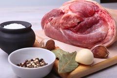 Rå grisköttknoge, aromatiska torkade lagerbladar, vitlök, salt hav och kryddor på en skärbräda Selektivt fokusera Ordna till för Royaltyfria Foton