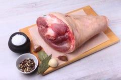 Rå grisköttknoge, aromatiska torkade lagerbladar, vitlök, salt hav och kryddor på en skärbräda Selektivt fokusera Ordna till för Royaltyfri Fotografi