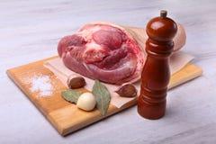 Rå grisköttknoge, aromatiska torkade lagerbladar, vitlök, salt hav, pepparmolar och kryddor på en skärbräda selektivt Arkivfoton