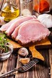 Rå grisköttskivor på en skärbräda Arkivbilder