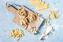 Rå gul italiensk pastapappardelle, fettuccine eller tagliatelle på en blå bakgrund, slut upp fotografering för bildbyråer