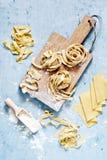 Rå gul italiensk pastapappardelle, fettuccine eller tagliatelle på en blå bakgrund, slut upp arkivfoto