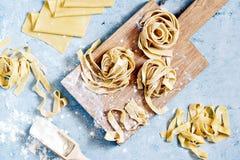 Rå gul italiensk pastapappardelle, fettuccine eller tagliatelle på en blå bakgrund, slut upp royaltyfria bilder
