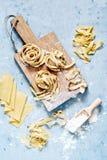 Rå gul italiensk pastapappardelle, fettuccine eller tagliatelle på en blå bakgrund, slut upp royaltyfri fotografi