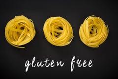 Rå gul pasta med text som är skriftlig på den svart tavlan Gluten frigör Arkivbild