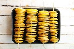 Rå gula potatisar i en peel, snitt in i skivor Stycken strängas på trästeknålar som ut horisontellt läggas i fyra rader Arkivfoto