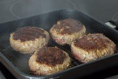 Rå hamburgare, nötkött i en stekpanna på matlagningyttersida i kök fotografering för bildbyråer