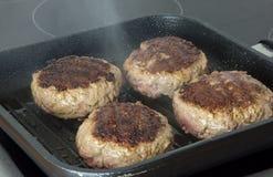 Rå hamburgare, nötkött i en stekpanna på matlagningyttersida i kök arkivfoto