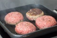 Rå hamburgare, nötkött i en stekpanna på matlagningyttersida i kök royaltyfria bilder