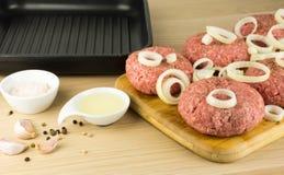 Rå hamburgare, nötkött på ett cooting bräde, stekpanna på woogenbackg arkivbild