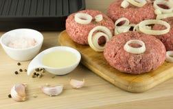 Rå hamburgare, nötkött på ett cooting bräde, stekpanna på woogenbackg royaltyfri foto