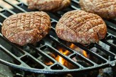 Rå hamburgare på grillfestgaller med brand Fotografering för Bildbyråer