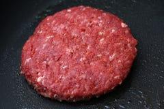 Rå hamburgare på kastrullen arkivfoton