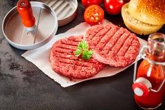 Rå hamburgaresmå pastejer med press och toppningar Royaltyfri Foto