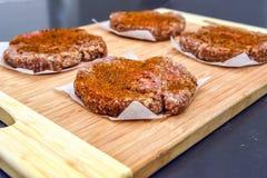 Rå hamburgaresmå pastejer på skärbrädacloseupen arkivbild