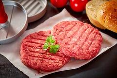 Rå hamburgaresmå pastejer som överträffas med ny persilja Fotografering för Bildbyråer