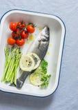 Rå havsbas, körsbärsröda tomater och sparris i bakplåten Ingredienser för lunch En torr frukost i en sked Arkivfoto