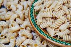 rå hel-korn pasta i en platta på en vide- torkduk på tabellen Top beskådar arkivfoton