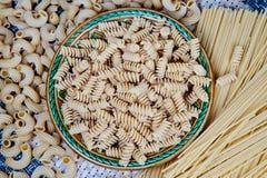 rå hel-korn pasta i en platta på en vide- torkduk på tabellen Top beskådar royaltyfri fotografi