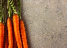 Rå hela nya morötter på grå bakgrund royaltyfri foto
