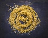 Rå hemlagad pasta, fodrad cirkel i mitten av sammansättningen på trälantligt slut för bästa sikt för bakgrund upp Arkivbilder