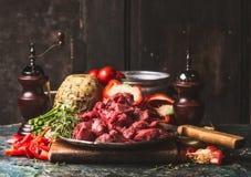 Rå huggen av nötköttgulasch av unga tjurar med grönsaker och matlagningingredienser på det mörka lantliga köksbordet arkivfoto