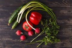 Rå ingredienser - blomkål, potatis, zucchini, morot, lök, peppar som lagar mat grillade grönsaker På en mörk träbakgrund Royaltyfri Foto