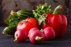 Rå ingredienser - blomkål, potatis, zucchini, morot, lök, peppar som lagar mat grillade grönsaker På en mörk träbakgrund Arkivfoto