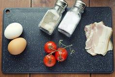Rå ingredienser för förvanskade ägg, den nya formeln, äggbacontomater saltar och pepprar på den bästa sikten för skärbrädan arkivbild