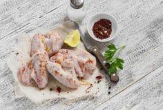 Rå ingredienser som förbereder kryddiga fega vingar, kryddor som är salta, persilja, fega vingar Arkivbild