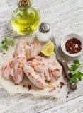 Rå ingredienser som förbereder kryddiga fega vingar - kryddor som är salta, persilja, fega vingar Arkivfoto