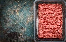 Rå köttfärs i plast- ask på lantlig bakgrund, bästa sikt fotografering för bildbyråer