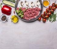 Rå köttfärs med champinjoner i en panna, peppar, tomater på en filial, kryddor, gurkor gränsar, textområde, på trälantligt Royaltyfri Bild