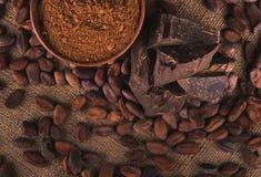 Rå kakaobönor, lerabunke med kakaopulver, choklad på säcken Royaltyfri Foto