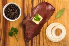 Rå kalvköttlever på träbräde med smör, löken, svartpeppar, lager och persilja Arkivbild