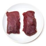 Rå kamelköttbiffar på plattan Royaltyfria Bilder