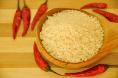 Rå korta ris på träskeden med någon chili royaltyfri foto