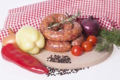 Rå korv med röda och gula peppar, lökar, cerium, peppar royaltyfri foto