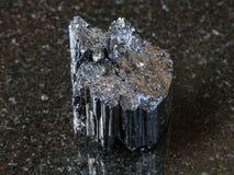 Rå kristall av den svarta tourmalinen Schorl på mörker Royaltyfri Bild