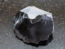 rå kristall för obsidian (vulkaniskt exponeringsglas) på mörker Arkivbild