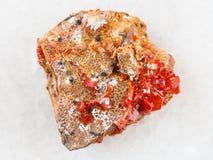 rå kristaller av Vanadinite på stenen på vit Arkivfoto