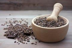 Rå krossade bönor för kakaostift i mortelstöt Arkivbild
