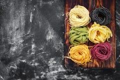 Rå kulör tagliatelle och spagetti på svart bakgrund royaltyfri fotografi