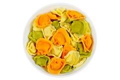 Rå kulör tortellini i en bunke, vit bakgrund Arkivfoton