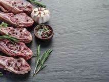 Rå lammkotletter med vitlök och örter royaltyfria foton
